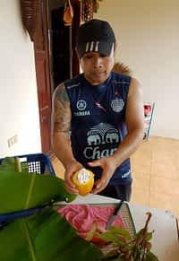 Amorn from discovery garden Nong Khai holding an open cocoa pod.