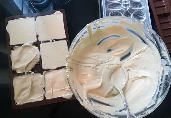 Spooning white chocolate into moulds. A big bowl of white chocolate and some moulds.